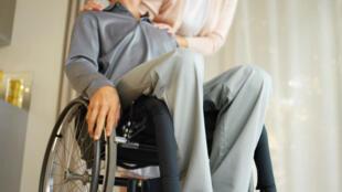 Un homme en fauteuil roulant accompagné de sa femme.