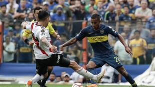 El jugador del River Plate Enzo Perez disputa un balon con el futbolista del Boca Juniors, el colombiano Sebastian Villa , durante el trnascurso del primer partido de la final de la Copa Libertadores 2018.