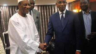 Le président guinéen Alpha Condé (G) et l'opposant Cellou Dalein Diallo (D) après leur réunion, au palais présidentiel, le 2 avril 2018.