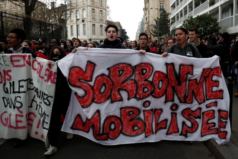 """Alunos e alunos do ensino médio participam de uma manifestação para protestar contra o plano de reforma do governo francês, em Paris, em 11 de dezembro de 2018. O slogan diz """"A universidade de Sorbonne se mobiliza""""."""