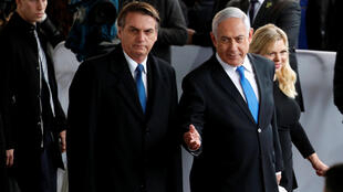 Israeli Prime Minister Benjamin Netanyahu gestures as he stands next to Brazilian President Jair Bolsonaro during a welcoming ceremony upon his arrival in Israel, at Ben Gurion International airport on 31 March, 2019.