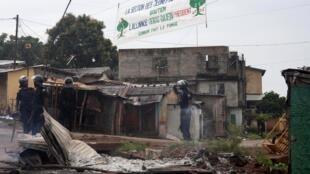 Des policiers dégagent un barrage établi par des partisans du candidat à la présidentielle en Guinée, Cellou Dalein Diallo, à Conakry.