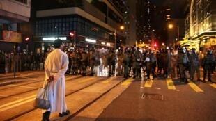 Một linh mục bình thản đương đầu với cảnh sát chống bạo động, trong một cuộc biểu tình chống dự luật dẫn độ ở Kennedy Town (Kiên Ni), Hồng Kông ngày 04/08/2019.