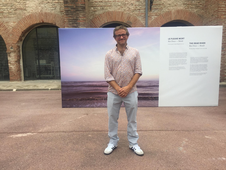 Samuel Bollendorff diante de uma foto sua do Rio Doce.