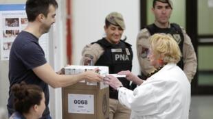 Une femme glisse son bulletin dans une urne dans un bureau de vote à Buenos Aires, le 27 octobre 2019.
