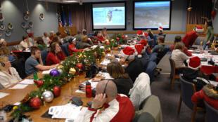 Voluntários atendem telefonemas de crianças sobre papai Noel.
