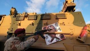 Un membre de l'Armée nationale libyenne (LNA) commandée par Khalifa Haftar pointe son arme sur l'image du président turc Tayyip Erdogan pendu à un véhicule blindé militaire turc.