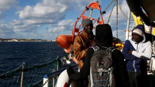 Des rescapés avec un journaliste à bord d'un des deux navires humanitaires de Sea Watch, bloqués en mer près de Malte, le 4 janvier 2019.