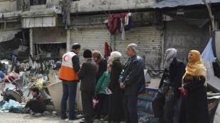 A Damas, des habitants attendent pour recevoir de l'aide humanitaire au camp de réfugiés palestiniens de Yarmouk, le 11 mars 2015.