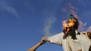 Des manifestants brûlent un mannequin représentant un travailleur grec, lors du rassemblement du dimanche 28 avril à Athènes.
