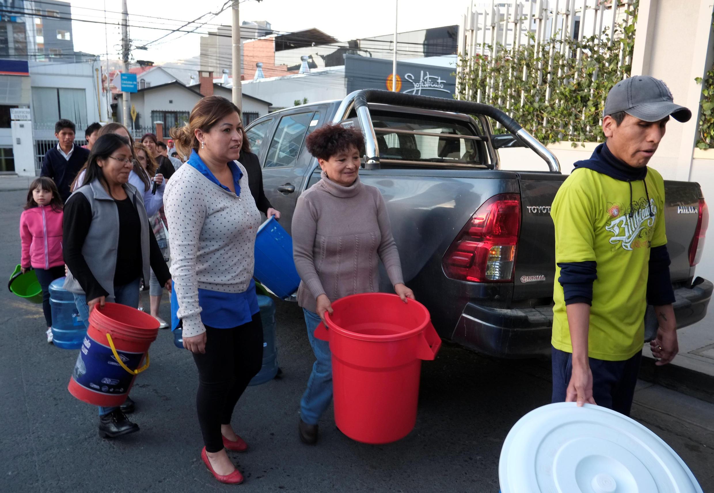 Bolivianos fazem fila para encher baldes de água de caminhão-pipa