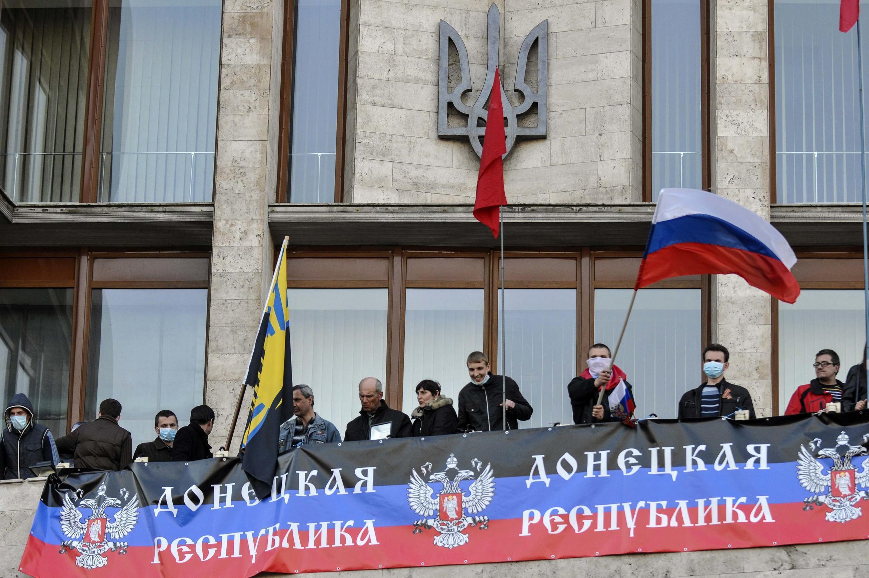 Manifestantes pró-russos penduram bandeira da Rússia em prédio público do governo ucraniano em Donetsk.