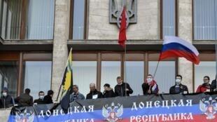 បាតុករអ្នកគាំទ្ររុស្ស៊ីនាំគ្នាគ្រវីទង់ជាតិរុស្ស៊ី នៅលើអគាររដ្ឋាភិបាលតំបន់ Donetsk ភាគខាងកើតអ៊ុយក្រែន