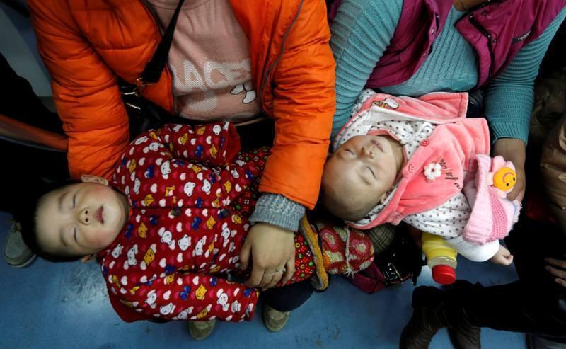 在母亲怀中熟睡的两个孩子2013年3月1日北京地铁。