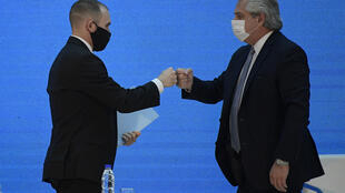 El presidente de Argentina, Alberto Fernández (derecha) y el ministro de Economía, Martín Guzmán, se saludan con los puños tras anunciar la reestructuración de una deuda extranjera de 66.000 millones de dólares, durante una ceremonia en el Palacio Presidencial de la Casa Rosada en Buenos Aires, el 31 de agosto de 2020.