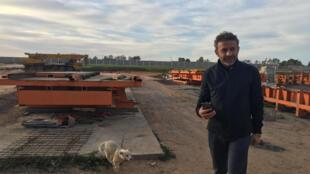 """Sinan Kava, dirigeant de """"Karanfil Construction"""" devant le chantier d'usine à béton qui """"sera prête d'ici un mois""""."""