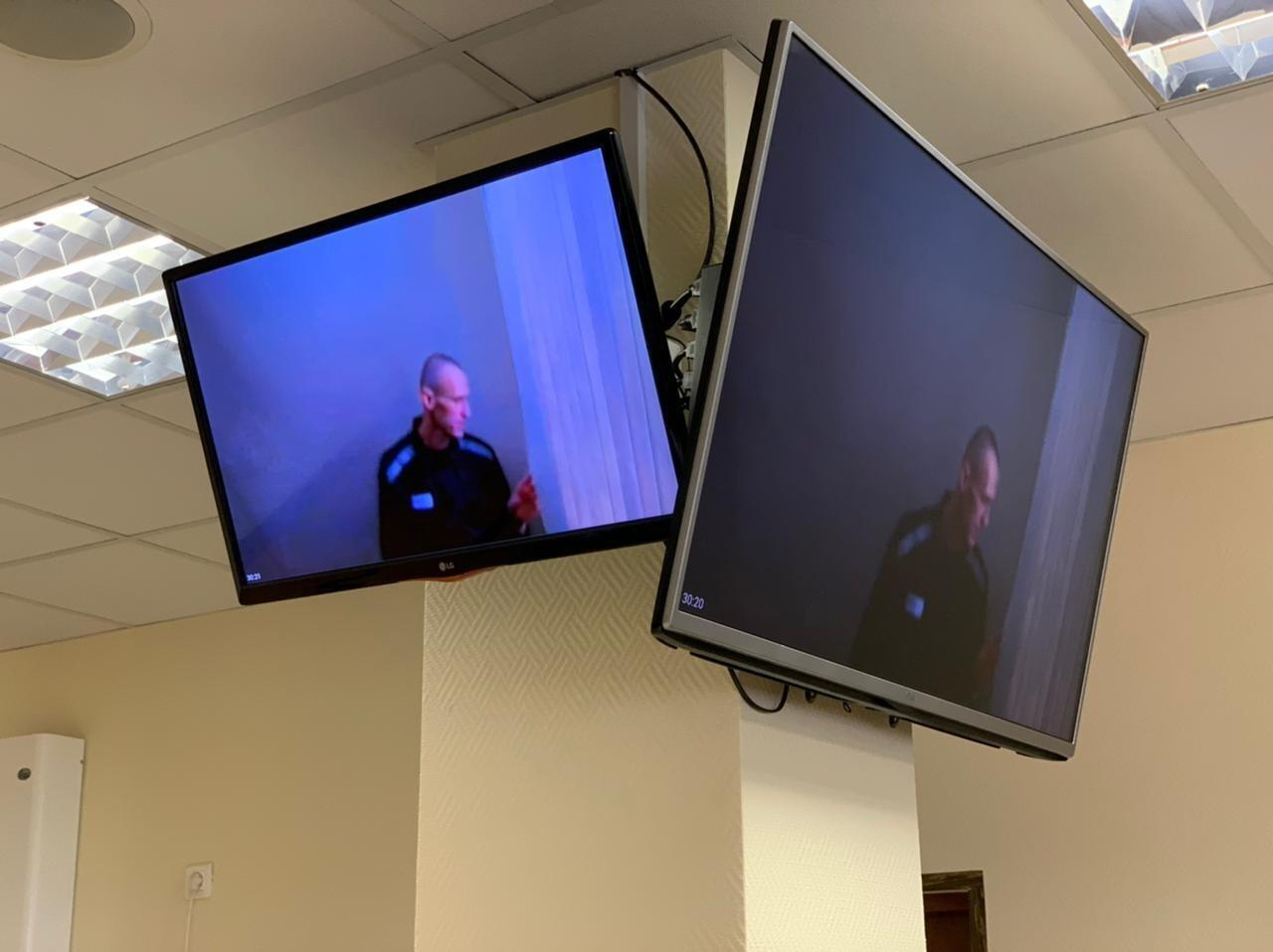 In this photo provided by the Babuskinsky District Court on Thursday, April 29, 2021, Russian opposition leader Alexei Navalny appears on TV screens via a video link from prison, during a hearing on his charges for defamation, in the Babuskinsky District Court in Moscow, Russia. The politician was convicted in February and ordered to pay a fine of 850-thousand rubles (the equivalent of $11,500). It was Navalny's first public appearance since his transfer to a penal colony last month. (Babuskinsky District Court Press Service via AP)