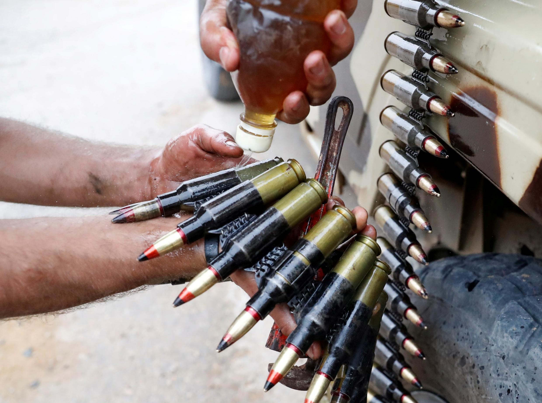 Un combattant du GNA huile des balles lors d'affrontements avec des forces du maréchal Haftar dans les alentours de Tripoli, en mai 2019 (image d'illustration).