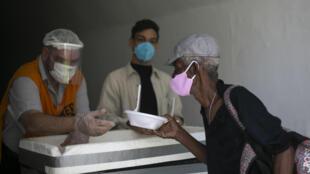 Idoso recebe refeição no Rio de Janeiro durante pandemia de Covid-19