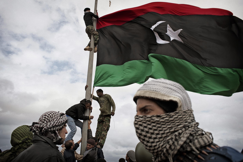Des rebelles libyens hissent leur drapeau à un poste-frontière. Ras Lanouf, Libye, 8 mars 2011.