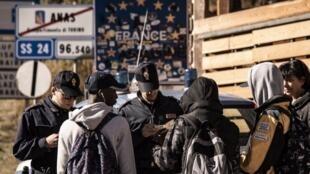 Des douaniers italiens contrôlent les papiers de trois migrants le 21 octobre 2018 à Claviere.
