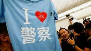 """香港示威者在機場圍毆兩名內地男展示其中一人""""我愛警察""""T恤衫2019年8月13日"""