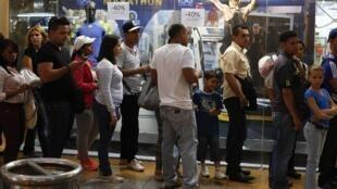 Venezuelanos fazem filas diante das lojas depois do presidente Nicolás Maduro ter baixado os preços em até 50%.