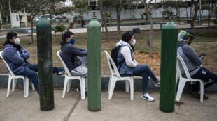 Familiares de pacientes de COVID-19 hacen fila a la espera de recargar sus botellas de oxígeno en Villa María del Triunfo, en el sur de Lima
