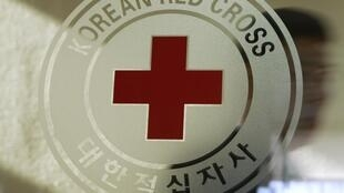 A man walks past a logo of the South Korean Red Cross at its headquarters in Seoul 9 February 2011.