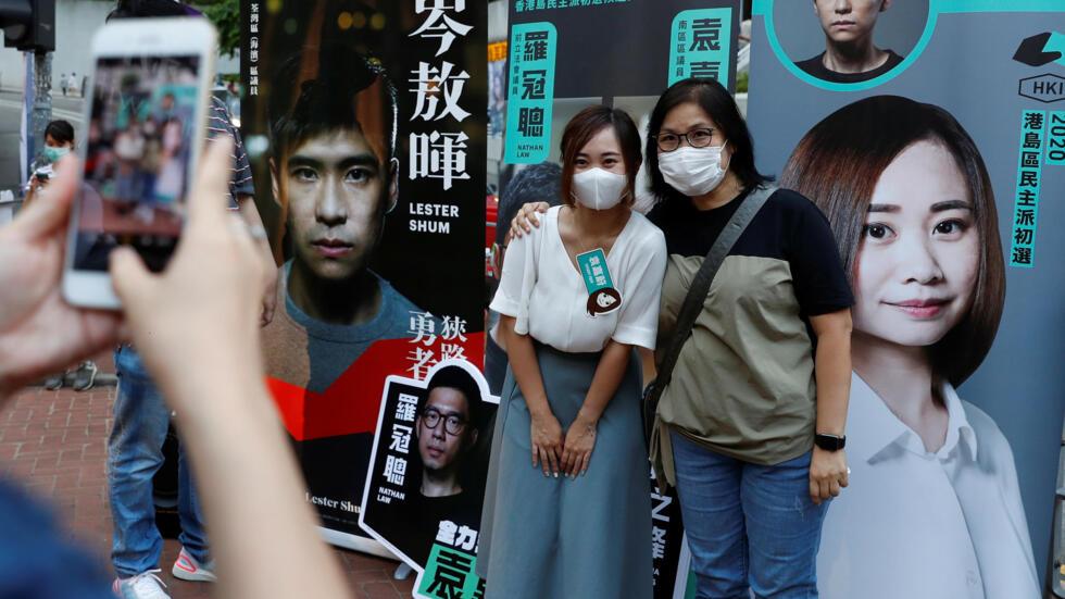 香港民主派7月11日首日初选,港人积极参加投票,并与他们支持的候选人或在候选人的招贴画前合影。