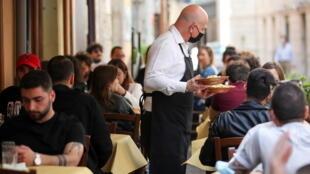 """Almuerzo en la terraza de un restaurante, ahora que gran parte de Italia se convirtió en """"zona amarilla"""", aliviando las restricciones debidas a la Covid-19 y permitiendo que los bares y restaurantes sirvan a los clientes en mesas al aire libre, en Roma, el 26 de abril de 2021."""