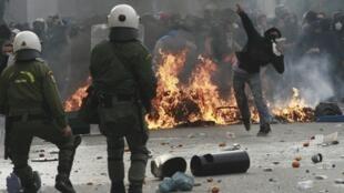 Un jeune lance des pierres aux policiers, dans le centre d'Athènes, le 6 décembre 2009.
