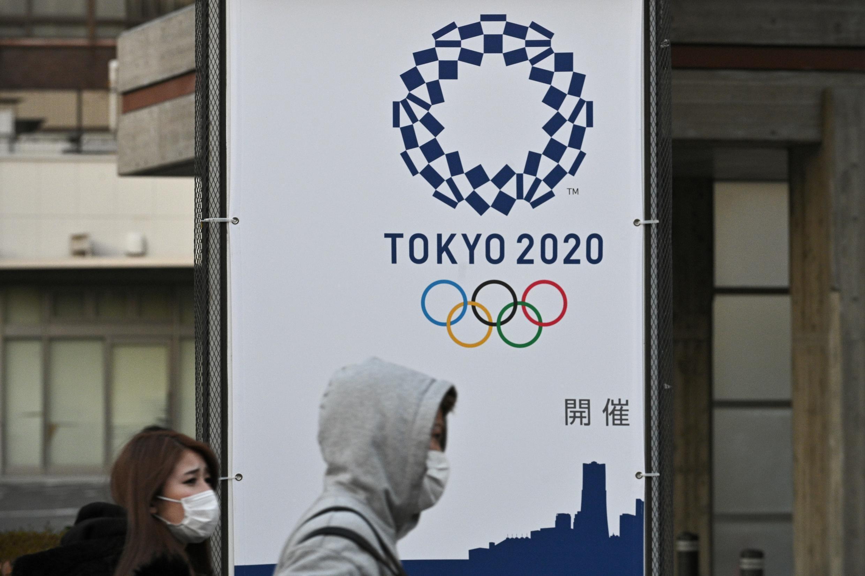 Des piétons portant des masques de protection passent devant un panneau publicitaire pour les Jeux Olympiques 2020 de Tokyo, le 16 mars 2020 à Yokohama pendant l'épidémie du nouveau coronavirus au Japon