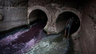 Au cœur de Dacca, un conduit d'égout décharge les eaux usées provenant de la vieille ville, tandis que l'autre déverse les déchets chimiques produits par une usine de peinture.