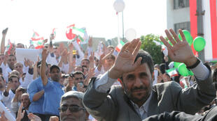 Ahmadinejad waves his hands as he greets Lebanese Hezbollah supporters in Beirut