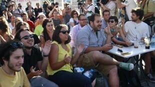 Reunidos em uma praça no centro de Atenas, simpatizantes do Syriza celebram as projeções favoráveis à esquerda radical divulgadas pela televisão neste domingo, 17 de junho de 2012.