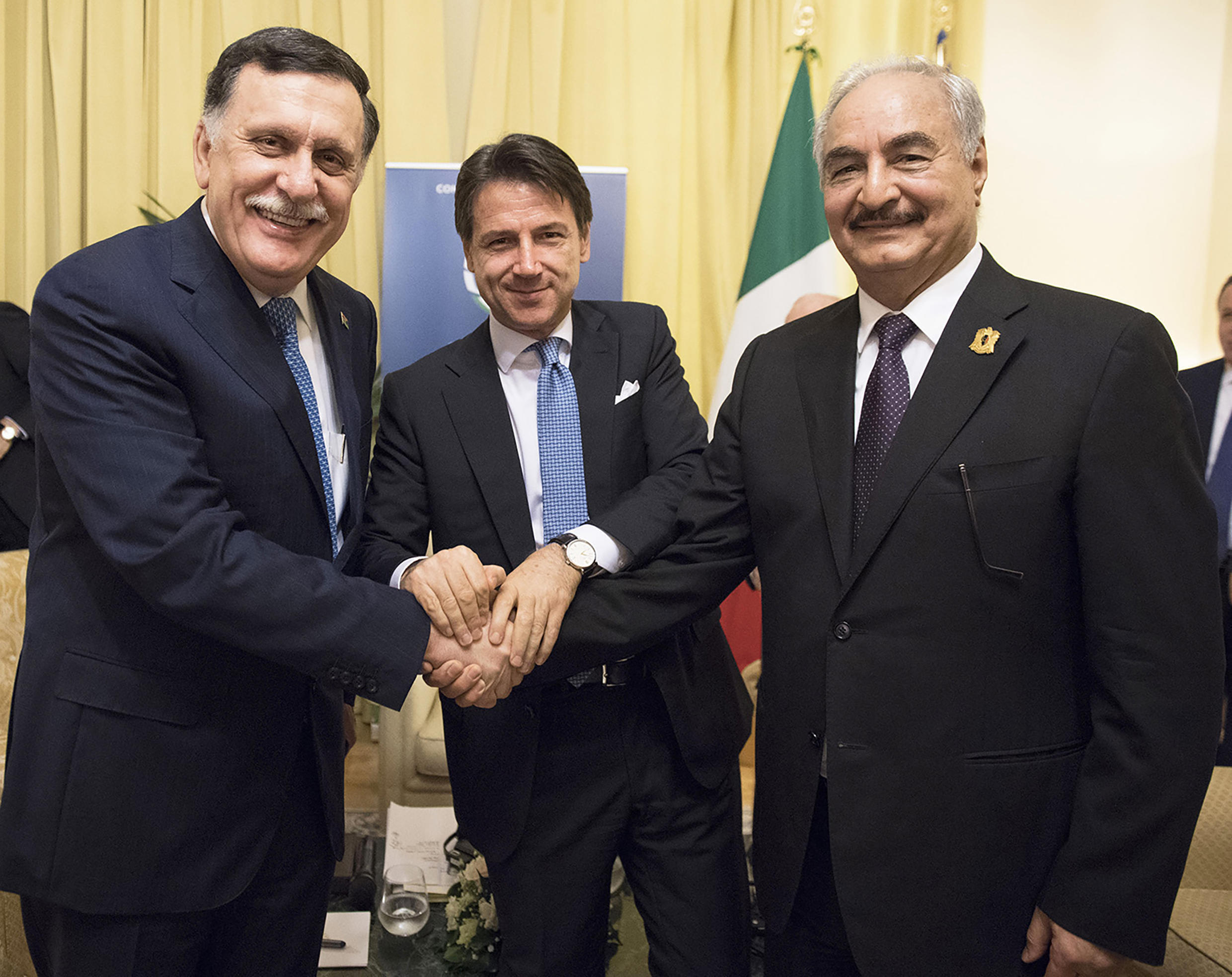 Fayez al-Sarraj (left) and Khalifa Haftar (right) pose for a photo with Italian Prime Minister Giuseppe Conte (centre) during a meeting in Palermo on 13 November 2018.