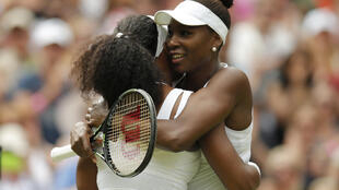 Serena Williams and her sister Venus Williams embrace after their fourth-round match, 6 July 2015
