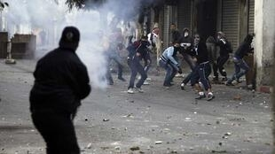 A riot police officer fires tear gas at protesters during clashes in Belcourd district of the capital Algiers