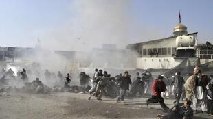 People react seconds after a suicide blast targeting a Shi'ite Muslim gathering in Kabul