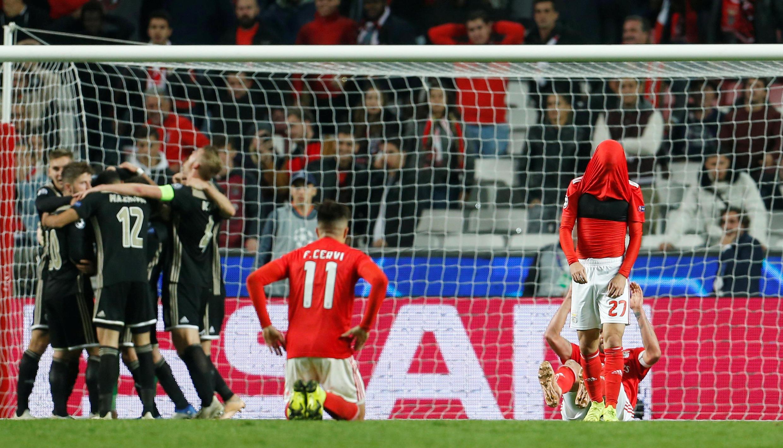 Jogadores do Benfica, com as camisolas encarnadas, estão desesperados após o empate a uma bola frente ao Ajax, que atrapalhou as contas dos lisboetas para os oitavos da liga milionária.