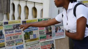 Mulher observa jornais na Costa do Marfim.
