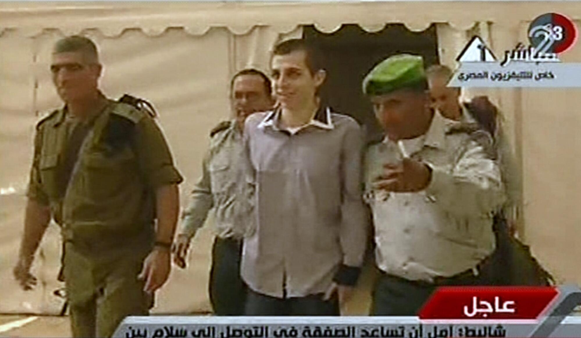 Soldado Gilad Shalit é acompanhado por autoridades do Hamas antes de ser solto.