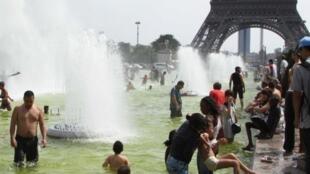 高温酷暑时,人们在埃菲尔铁塔前的水池中嬉水。