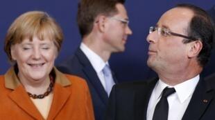 President Francois Hollande (R) and German Chancellor Angela Merkel make a photocall at the summit