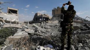 Một binh sĩ Syrai đang quay video khu trung tâm nghiên cứu khoa học gần Damas, bị phá hủy sau vụ tấn công của liên minh ba bên, ngày 14/04