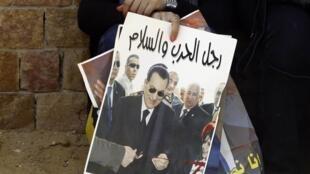 Sur la pancarte d'une pro-Moubarak, devant le palais de justice: «Moubarak, homme de guerre et de paix». Le Caire, le 11 mai 2013.