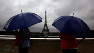 图为外国游客雨中远眺巴黎埃菲尔铁塔档案照片