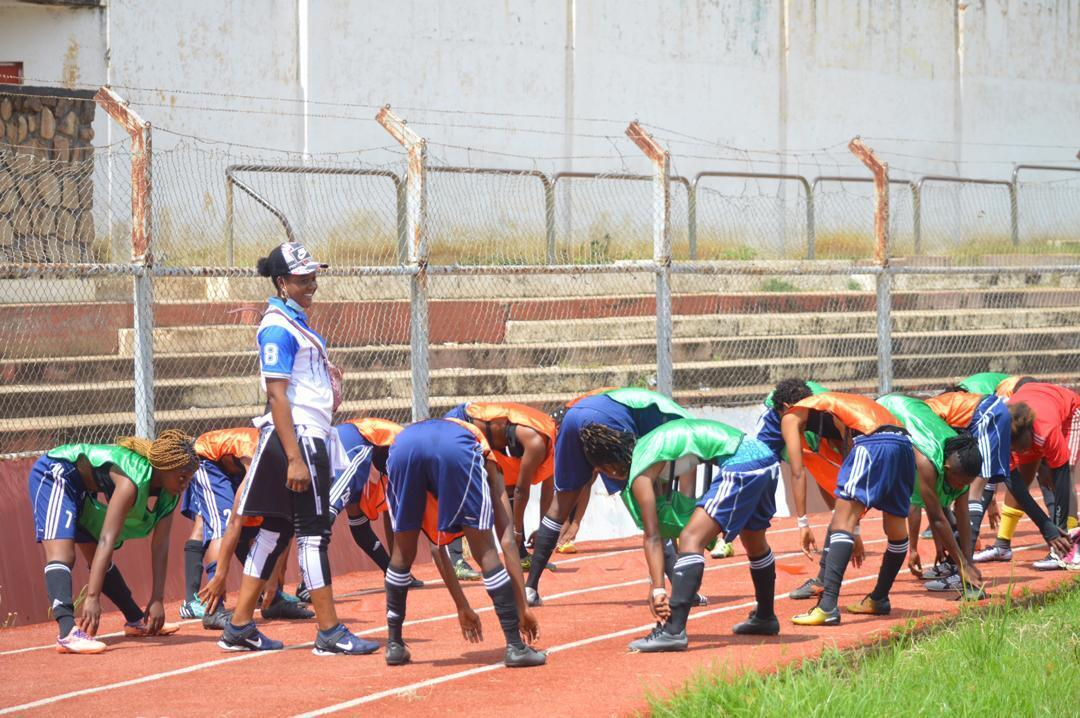 TP Mazembe women's coach Maguy Safi (standing) on the field