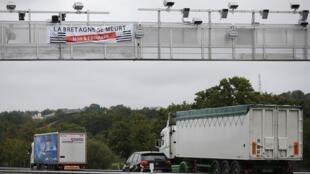 """Uma faixa com os dizeres: """"A Bretanha está morrendo"""" contra uma taxa sobre a circulação de veículos pesados em ponte na região da Bretanha na França."""
